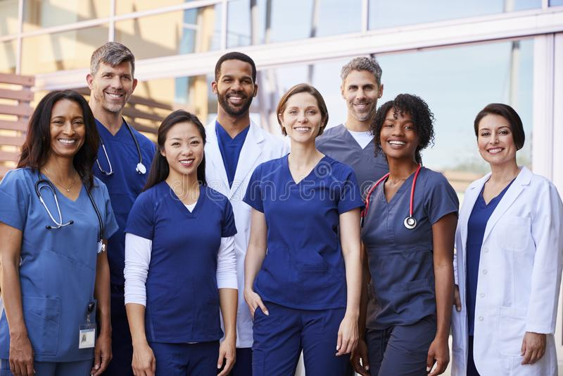 Χαμογελώντας ιατρική ομάδα που στέκεται μαζί έξω από ένα νοσοκομείο στοκ εικόνες