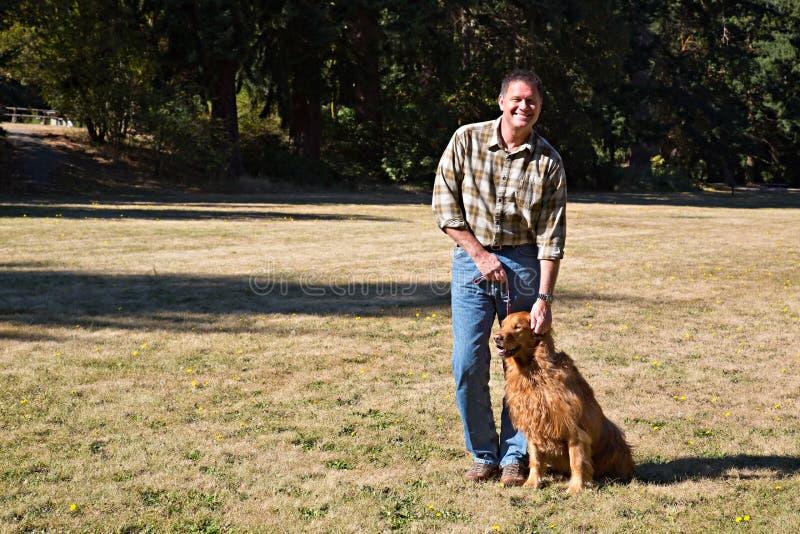 Χαμογελώντας ιδιοκτήτης σκυλιών στο πάρκο στοκ φωτογραφίες με δικαίωμα ελεύθερης χρήσης
