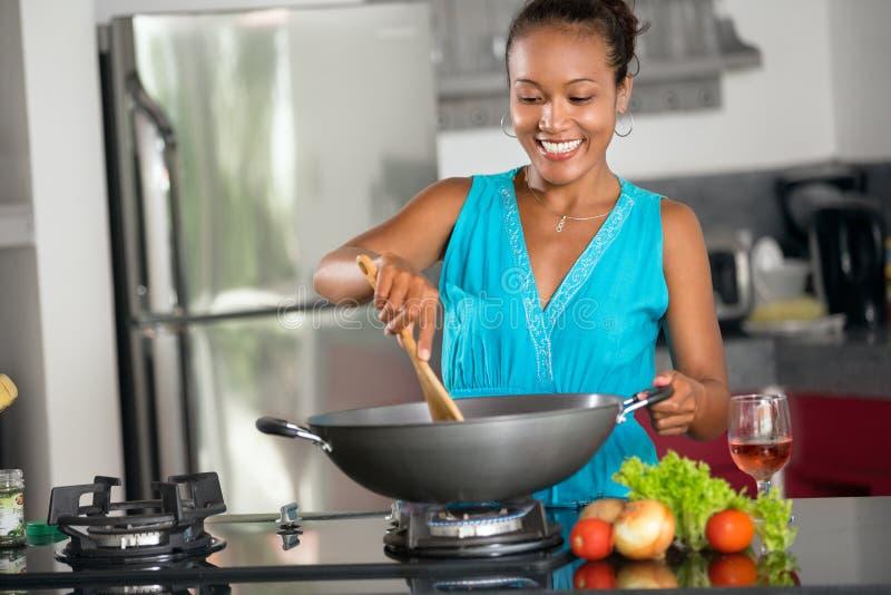Χαμογελώντας ινδονησιακή γυναίκα που κατασκευάζει τα τρόφιμα στο wok στοκ εικόνα