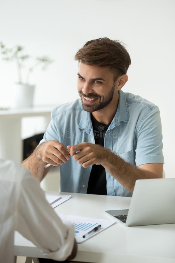 Χαμογελώντας καυκάσιος εργαζόμενος που γελά στον επιχειρησιακό συνάδελφο σε offic στοκ φωτογραφία με δικαίωμα ελεύθερης χρήσης