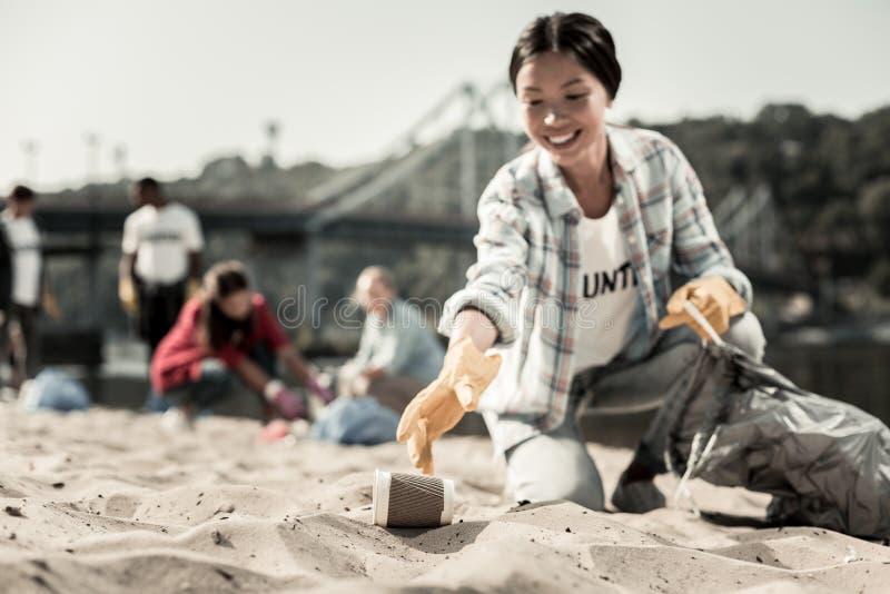 Χαμογελώντας κοινωνικά την ενεργό γυναίκα που φορά τα γάντια συλλέξτε τα κενά φλυτζάνια καφέ στην παραλία στοκ εικόνες