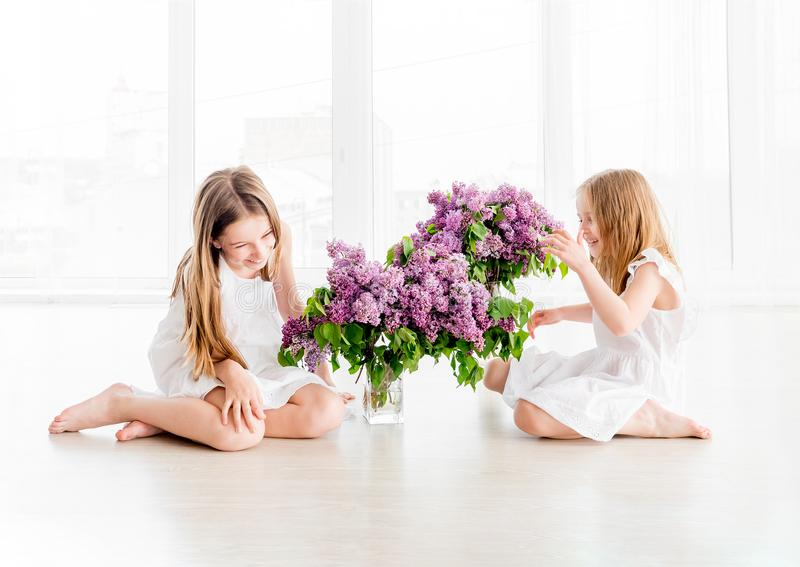 Χαμογελώντας κορίτσια παιδιών με την ιώδη ανθοδέσμη στοκ εικόνα
