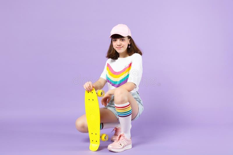 Χαμογελώντας κορίτσι εφήβων στα ζωηρά ενδύματα που κάθεται κίτρινο skateboard εκμετάλλευσης, που φαίνεται κάμερα που απομονώνεται στοκ εικόνες με δικαίωμα ελεύθερης χρήσης
