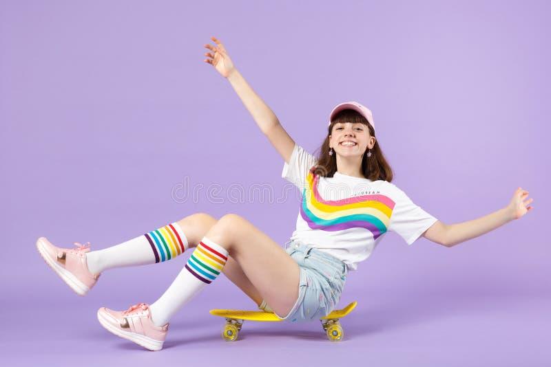 Χαμογελώντας κορίτσι εφήβων στα ζωηρά ενδύματα που κάθεται κίτρινο skateboard, χέρια διάδοσης που απομονώνονται στον ιώδη τοίχο κ στοκ εικόνα