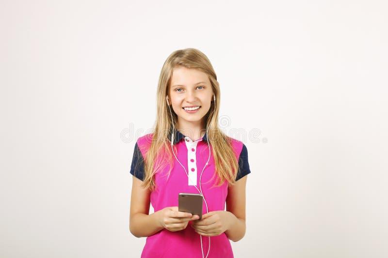 Χαμογελώντας κορίτσι εφήβων στην περιστασιακή τοποθέτηση εξαρτήσεων με το κινητό τηλέφωνο, παρουσίαση συγκινήσεων, που κάνουν τα  στοκ φωτογραφία με δικαίωμα ελεύθερης χρήσης
