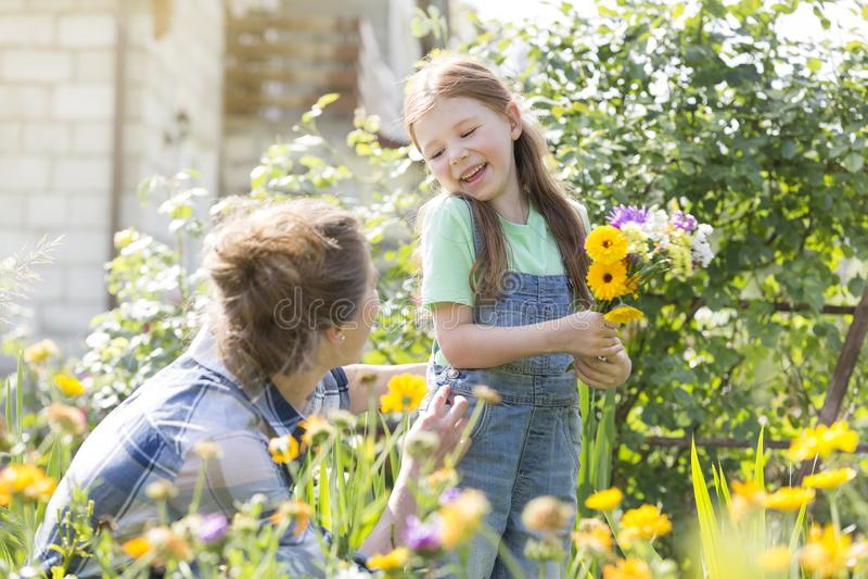 Χαμογελώντας κορίτσι με τα λουλούδια που εξετάζει τη μητέρα στο αγρόκτημα στοκ φωτογραφία με δικαίωμα ελεύθερης χρήσης