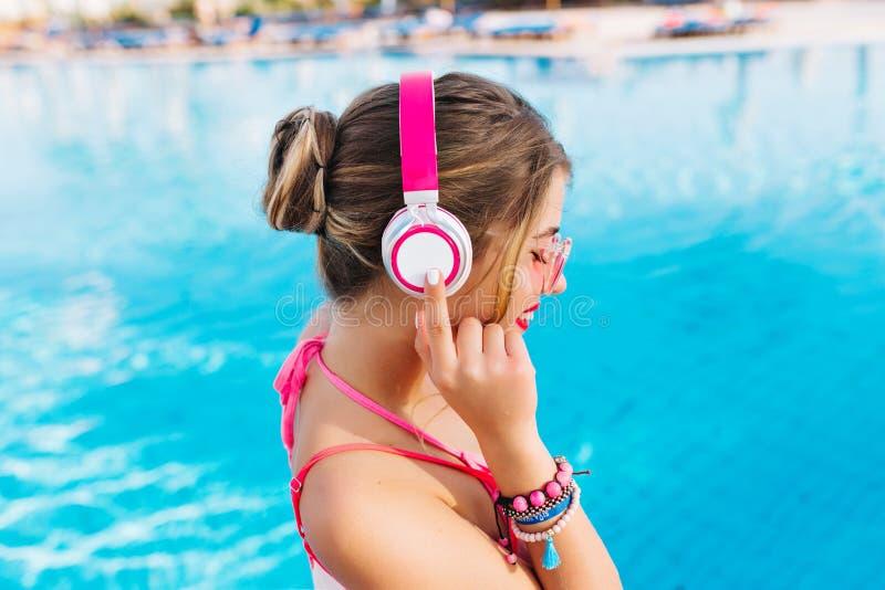 Χαμογελώντας κορίτσι με το καταπληκτικό μαύρισμα που κρατά τα νέα ακουστικά και την απόλαυση του Σαββατοκύριακου στο θερινό θέρετ στοκ εικόνες