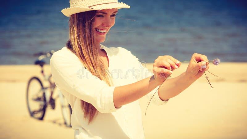 Χαμογελώντας κορίτσι με το λουλούδι στην παραλία στοκ φωτογραφίες