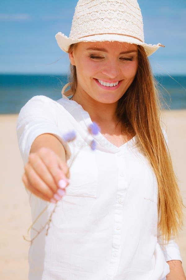 Χαμογελώντας κορίτσι με το λουλούδι στην παραλία στοκ εικόνα
