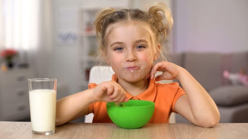 Χαμογελώντας κορίτσι που έχει το πρόγευμα και που εξετάζει τη κάμερα, γυαλί γάλακτος στον πίνακα, υγεία στοκ εικόνα