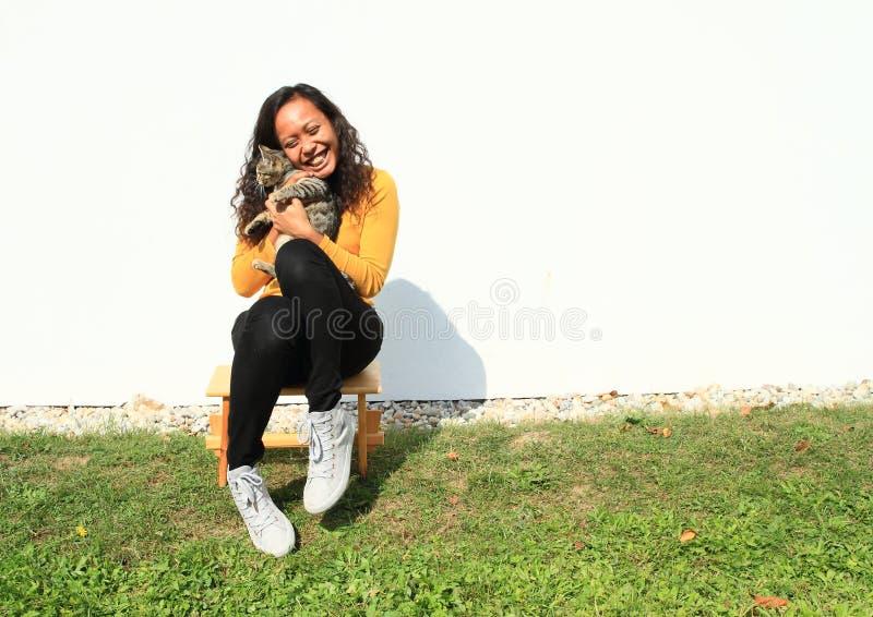 Χαμογελώντας κορίτσι που αγκαλιάζει μια γάτα στοκ φωτογραφία με δικαίωμα ελεύθερης χρήσης