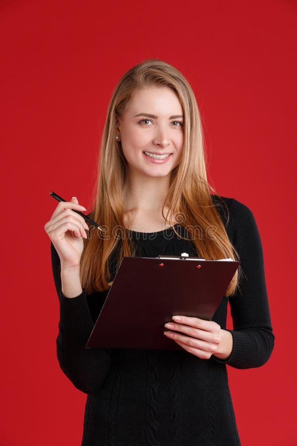 Χαμογελώντας κορίτσι, που κρατά μια περιοχή αποκομμάτων με τα έγγραφα και μια μάνδρα ballpoint στοκ εικόνα