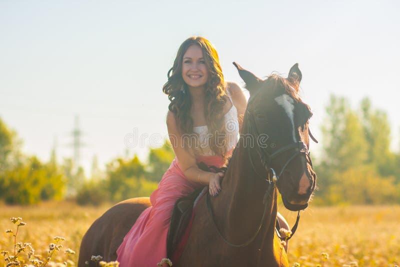 χαμογελώντας κορίτσι που οδηγά ένα άλογο σε ένα ροζ στοκ εικόνες