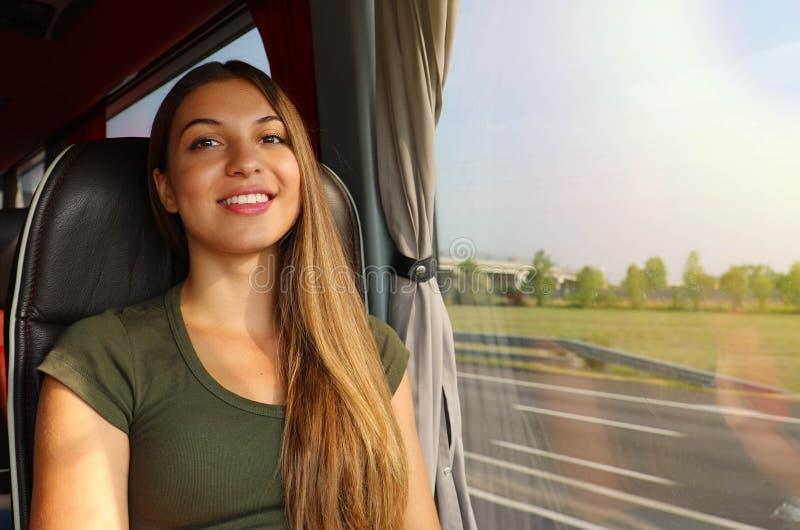 Χαμογελώντας κορίτσι που ταξιδεύει στο λεωφορείο με το δρόμο από το παράθυρο που εξετάζει τη κάμερα στοκ εικόνες με δικαίωμα ελεύθερης χρήσης
