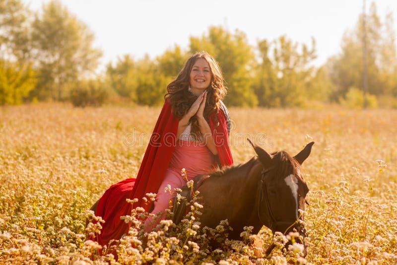 χαμογελώντας κορίτσι σε ένα άλογο σε έναν επενδύτη στοκ εικόνες