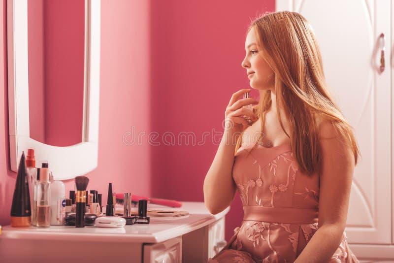 Χαμογελώντας κορίτσι σε ένα φόρεμα που κοιτάζει στον καθρέφτη και την εφαρμογή του αρώματος στοκ φωτογραφία με δικαίωμα ελεύθερης χρήσης