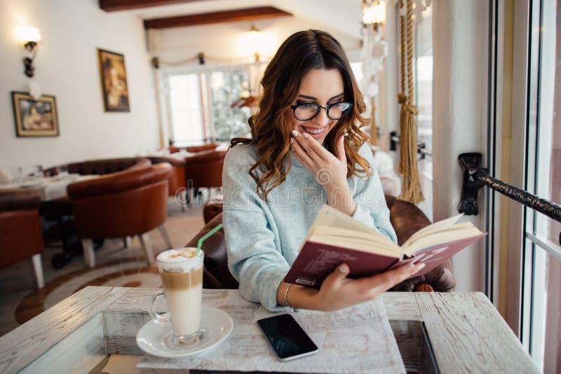 Χαμογελώντας κορίτσι στα γυαλιά που διαβάζει το βιβλίο στοκ εικόνες