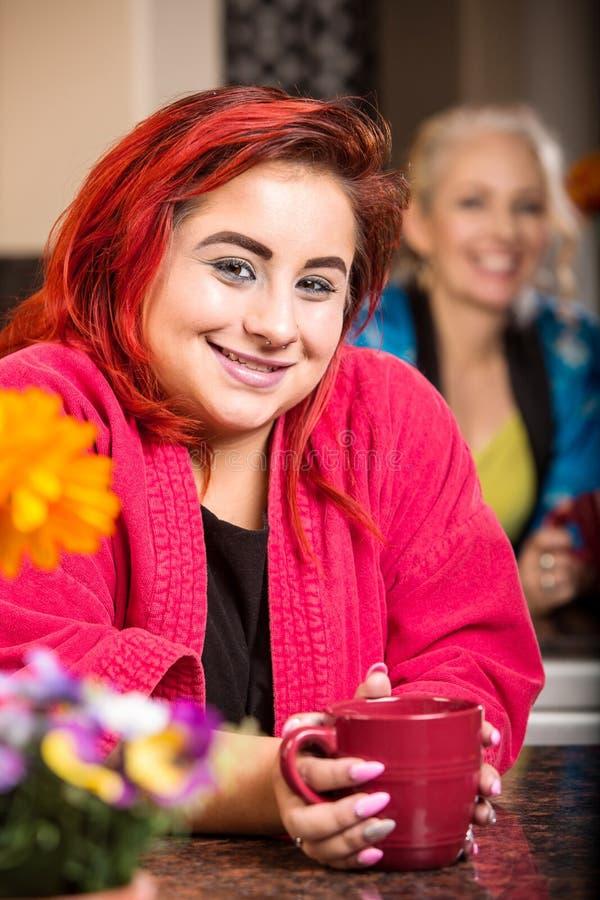 Χαμογελώντας κορίτσι στην κουζίνα με το mom στο υπόβαθρο στοκ φωτογραφία με δικαίωμα ελεύθερης χρήσης
