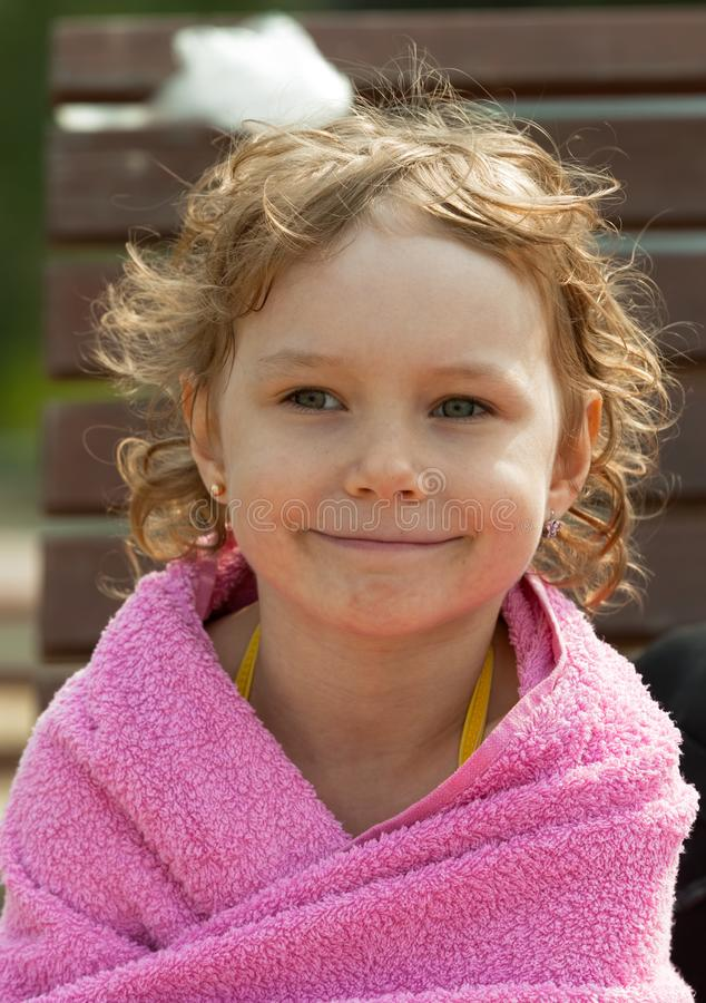 Χαμογελώντας κορίτσι στην πετσέτα σε υπαίθριο στοκ εικόνα