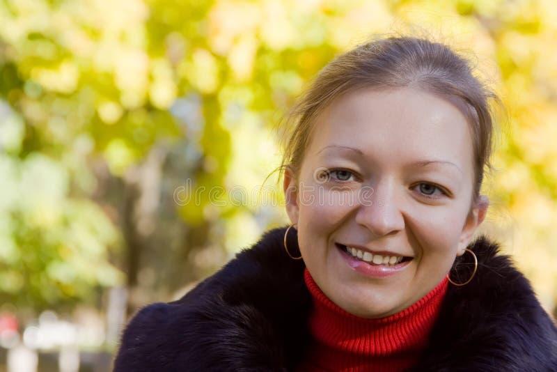 Χαμογελώντας κορίτσι στο πάρκο φθινοπώρου στοκ εικόνες με δικαίωμα ελεύθερης χρήσης