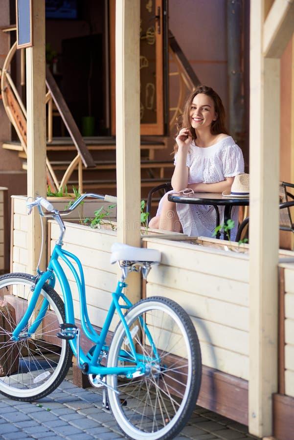 Χαμογελώντας κορίτσι στο πεζούλι του θερινού καφέ με το αναδρομικό ποδήλατο στοκ εικόνες