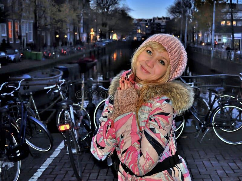 Χαμογελώντας κορίτσι στο ρόδινο σακάκι κοντά στο κανάλι του Άμστερνταμ στο μπλε βράδυ ώρας μεταξύ των ποδηλάτων στοκ εικόνες