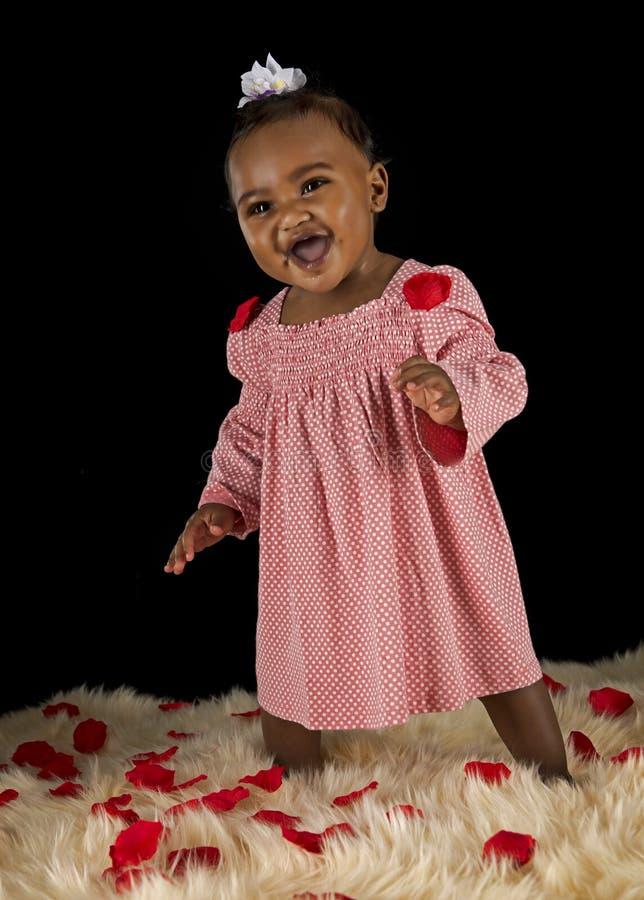 Χαμογελώντας κοριτσάκι που καλύπτεται με τα ροδαλά πεντάλια στοκ εικόνες