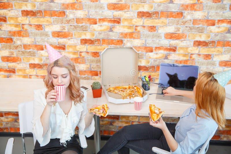 Χαμογελώντας κυρία γραφείων, στην ώρα μεσημεριανού γεύματος και κατανάλωση της πίτσας ατμόσφαιρα εορταστική στοκ φωτογραφία με δικαίωμα ελεύθερης χρήσης
