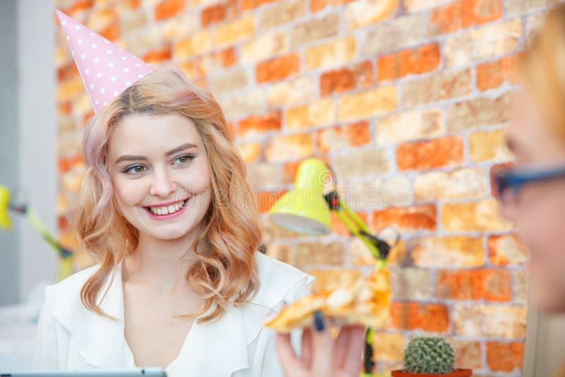 Χαμογελώντας κυρία γραφείων, στην ώρα μεσημεριανού γεύματος και κατανάλωση της πίτσας ατμόσφαιρα εορταστική στοκ εικόνες