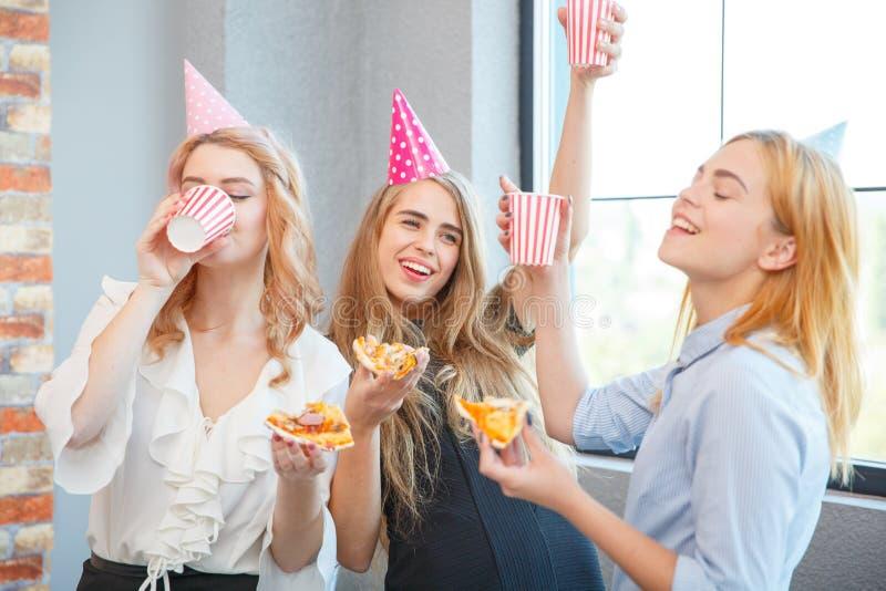 Χαμογελώντας κυρία γραφείων, στην ώρα μεσημεριανού γεύματος και κατανάλωση της πίτσας ατμόσφαιρα εορταστική στοκ εικόνα με δικαίωμα ελεύθερης χρήσης