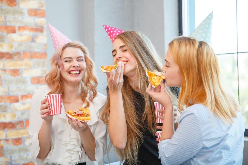 Χαμογελώντας κυρία γραφείων, στην ώρα μεσημεριανού γεύματος και κατανάλωση της πίτσας ατμόσφαιρα εορταστική στοκ φωτογραφίες