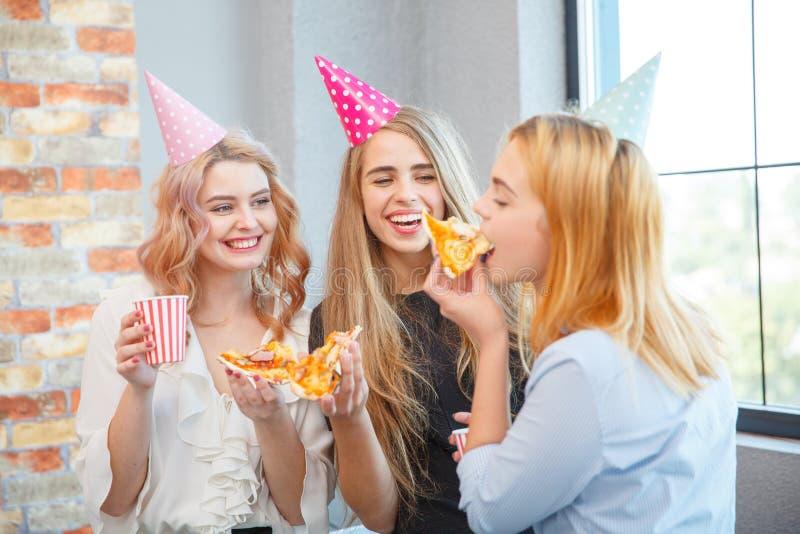 Χαμογελώντας κυρία γραφείων, στην ώρα μεσημεριανού γεύματος και κατανάλωση της πίτσας ατμόσφαιρα εορταστική στοκ φωτογραφία