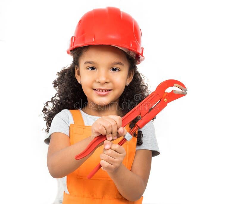 Χαμογελώντας λίγο κορίτσι-εργαζόμενο με τις πένσες στα χέρια που απομονώνεται στοκ εικόνες με δικαίωμα ελεύθερης χρήσης