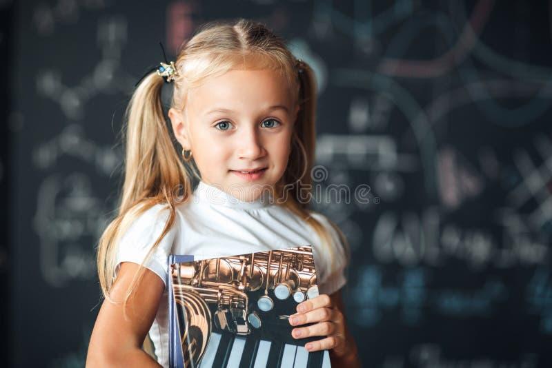 Χαμογελώντας λίγο ξανθό κορίτσι με την τρίχα που μαζεύεται στις ουρές, η άσπρη μπλούζα, και η γκρίζα φούστα κρατούν το βιβλίο σε  στοκ φωτογραφία με δικαίωμα ελεύθερης χρήσης