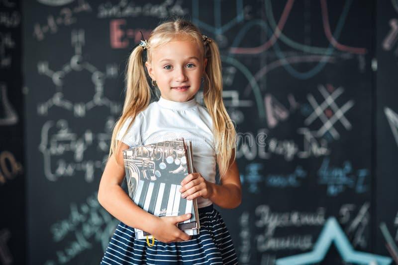 Χαμογελώντας λίγο ξανθό κορίτσι με την τρίχα που μαζεύεται στις ουρές, η άσπρη μπλούζα, και η γκρίζα φούστα κρατούν το βιβλίο σε  στοκ εικόνα