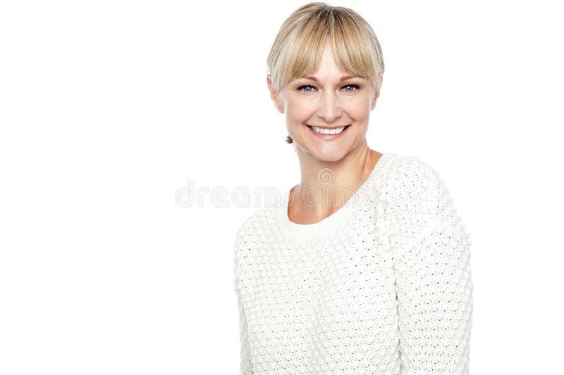 Χαμογελώντας μέση ηλικίας γυναίκα στην καθιερώνουσα τη μόδα ένδυση στοκ εικόνα