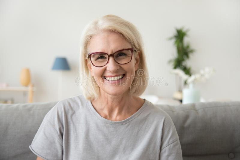 Χαμογελώντας μέση ηλικίας ώριμη γκρίζα μαλλιαρή γυναίκα που εξετάζει τη κάμερα στοκ εικόνα με δικαίωμα ελεύθερης χρήσης
