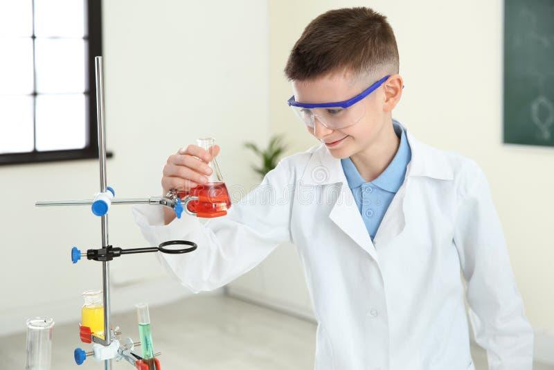 Χαμογελώντας μαθητής που εξετάζει τη φιάλη με το αντιδραστήριο στοκ φωτογραφίες