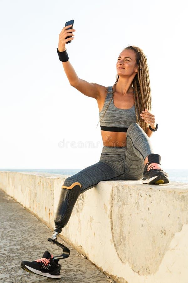 Χαμογελώντας με ειδικές ανάγκες γυναίκα αθλητών με το προσθετικό πόδι στοκ εικόνες με δικαίωμα ελεύθερης χρήσης