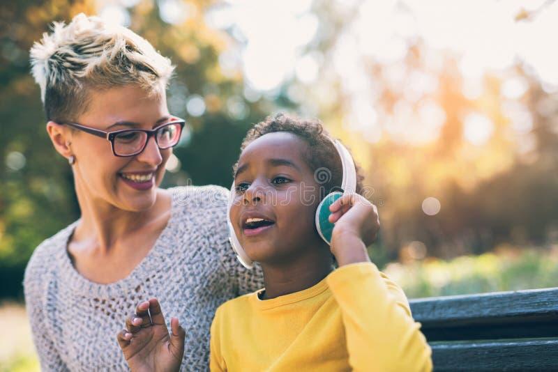 Χαμογελώντας μητέρα και λίγη κόρη που έχουν τη διασκέδαση, που ακούει τη μουσική στοκ φωτογραφία