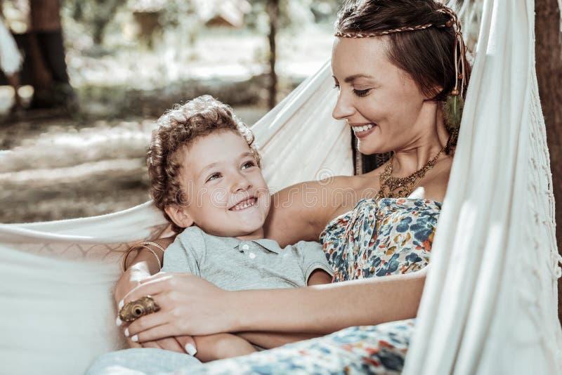 Χαμογελώντας μητέρα που μιλά με το γιο της για κάτι στοκ εικόνες