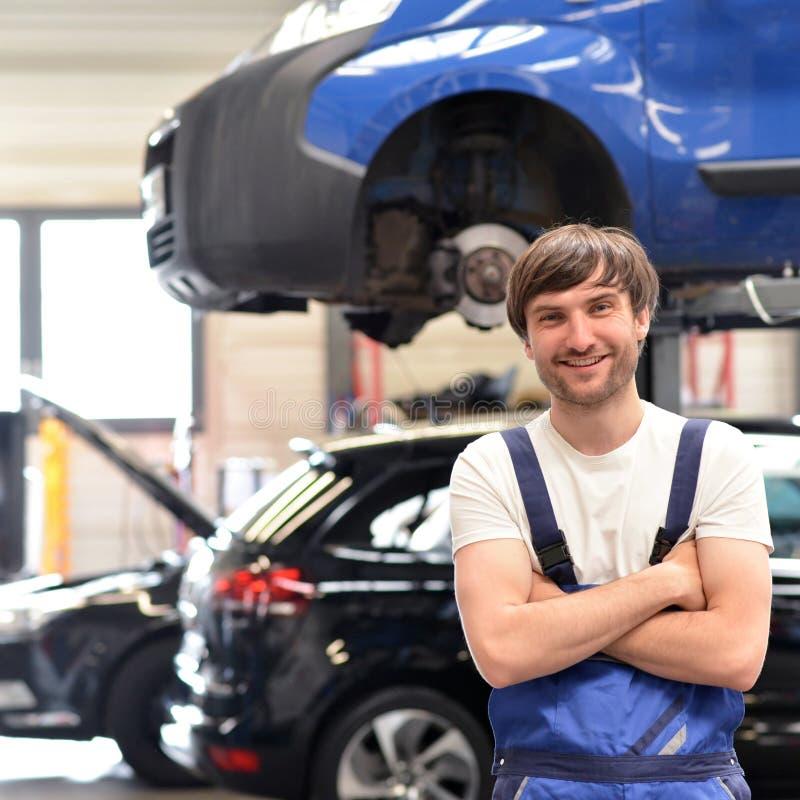 Χαμογελώντας μηχανικός αυτοκινήτων πορτρέτου σε ένα εργαστήριο - κινηματογράφηση σε πρώτο πλάνο με στο θόριο στοκ εικόνες
