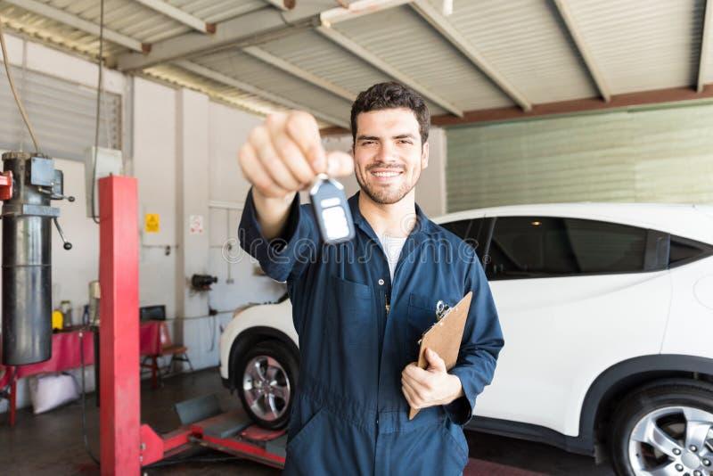 Χαμογελώντας μηχανικός που δίνει το κλειδί αυτοκινήτων στο αυτόματο κατάστημα επισκευής στοκ φωτογραφία με δικαίωμα ελεύθερης χρήσης