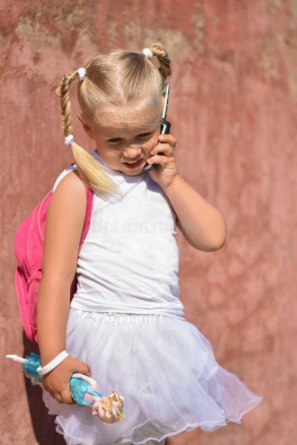 Χαμογελώντας μικρό κορίτσι με ένα σακίδιο πλάτης και παιχνίδι υπό εξέταση κοντά σε έναν παλαιό τοίχο στην οδό που καλεί με κινητό στοκ εικόνα