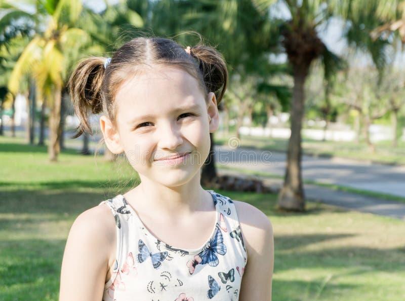 Χαμογελώντας μικρό κορίτσι με τα ponytails μεταξύ των φοινίκων στο όμορφο πορτρέτο της Ταϊλάνδης στοκ εικόνες