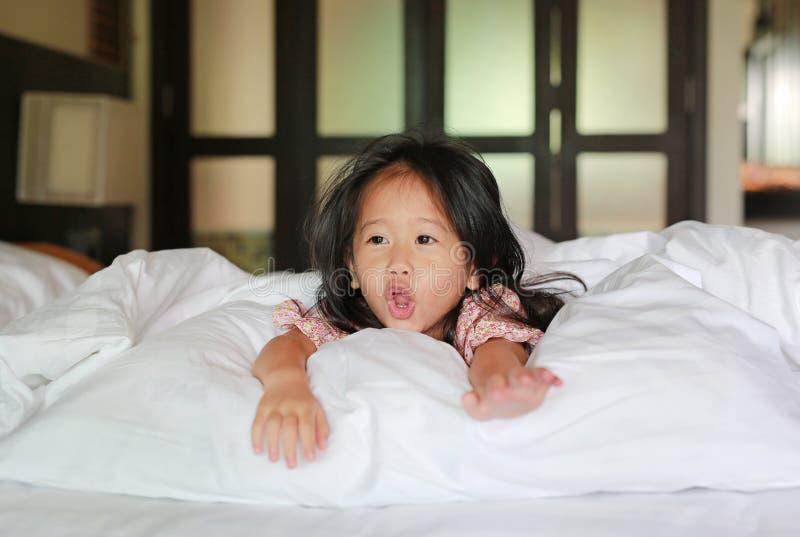 Χαμογελώντας μικρό κορίτσι που βρίσκεται κάτω από ένα άσπρο κάλυμμα στο κρεβάτι στοκ φωτογραφίες