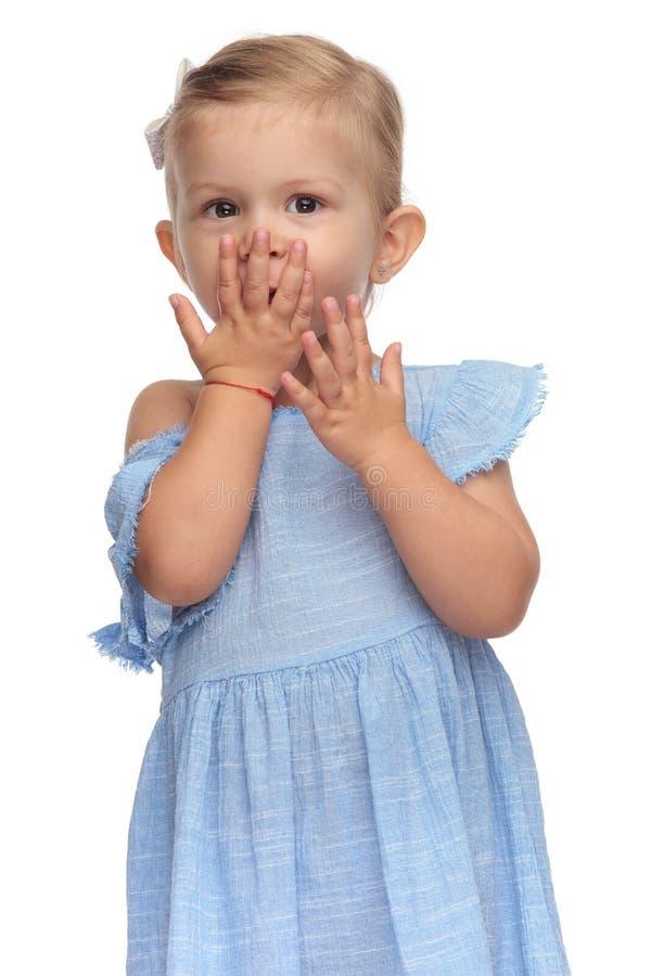 Χαμογελώντας μικρό κορίτσι που καλύπτει το στόμα της με ένα χέρι στοκ φωτογραφίες