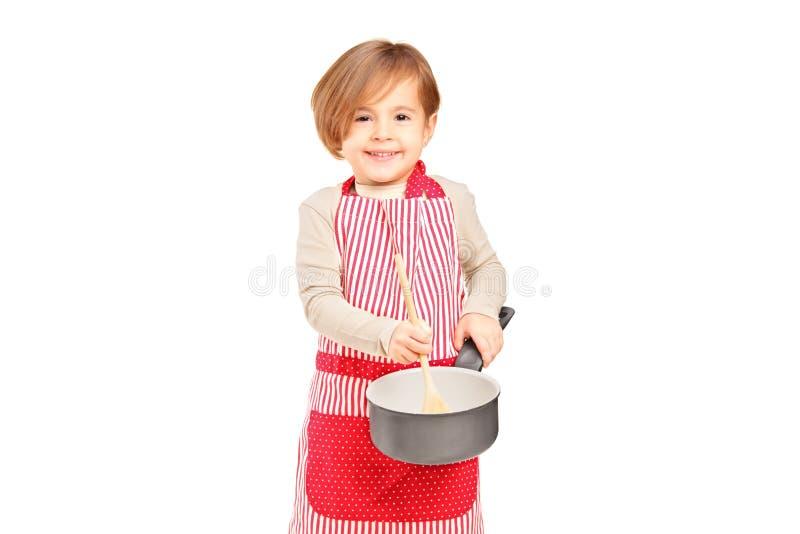 Χαμογελώντας μικρό κορίτσι που κρατά ένα τηγανίζοντας εργαλείο πανοραμικών λήψεων και κουζινών στοκ εικόνες