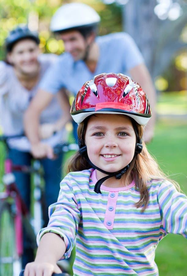 Χαμογελώντας μικρό κορίτσι που οδηγά ένα ποδήλατο στοκ εικόνα με δικαίωμα ελεύθερης χρήσης