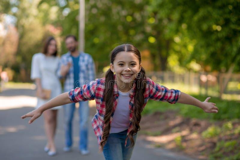Χαμογελώντας μικρό κορίτσι στο πάρκο με τις αγκάλες της ανοικτές Οι γονείς είναι υπόβαθρο στοκ φωτογραφίες με δικαίωμα ελεύθερης χρήσης